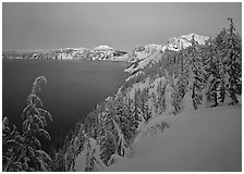 Snow-covered rim and trees, lake and mountains, dusk. Crater Lake National Park ( black and white)