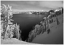 Snow-covered trees and dark lake waters. Crater Lake National Park ( black and white)