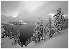 Snowy trees and lake with low clouds colored by sunset. Crater Lake National Park ( black and white)