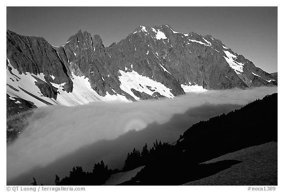 Sun projected on fog below peaks, early morning, Cascade Pass area, North Cascades National Park.  (black and white)