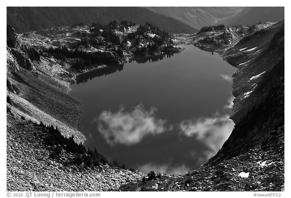 Fluffy clouds reflected in blue lake, North Cascades National Park.  (black and white)
