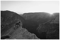 Hiker looking over the edge of the Diving Board, sunset. Yosemite National Park, California, USA. (black and white)