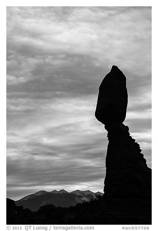 Balanced Rock silhouetted against La Sal Mountains and sky. Arches National Park, Utah, USA.