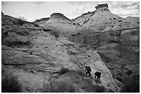 Hikers climbing out of High Spur slot canyon, Orange Cliffs Unit, Glen Canyon National Recreation Area, Utah. USA (black and white)