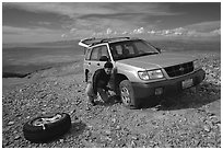Man changing a flat tire on remote spot at top of Mt Washington. Great Basin National Park ( black and white)