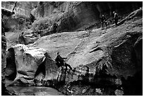 Canyoneers in wetsuits rappel down walls of the Subway. Zion National Park, Utah, USA. (black and white)