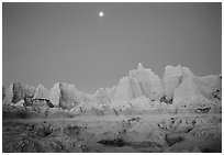 Moon and eroded badlands, Cedar Pass, dawn. Badlands National Park, South Dakota, USA. (black and white)