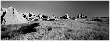 Badlands raising in tall grass prairie landscape, Cedar Pass. Badlands National Park (Panoramic black and white)