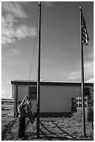 Ranger lowering Ogala Lakota flag, White River Visitor Center. Badlands National Park, South Dakota, USA. (black and white)
