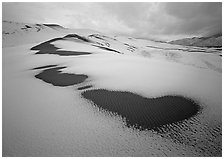 Patches of uncovered sand in snow-covered dunes, mountains, and dark clouds. Great Sand Dunes National Park, Colorado, USA. (black and white)