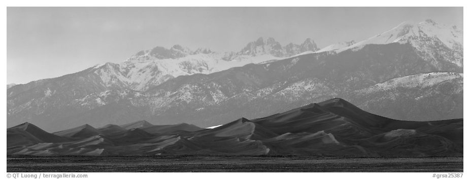 Sand dunes below snowy mountain range at sunset. Great Sand Dunes National Park and Preserve (black and white)