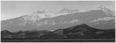 Sand dunes below snowy mountain range at sunset. Great Sand Dunes National Park and Preserve (Panoramic black and white)
