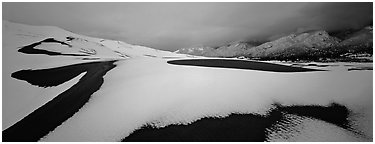 Snow-covered dune landscape and mountains at dawn. Great Sand Dunes National Park and Preserve (Panoramic black and white)