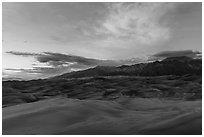 Dune field and Sangre de Cristo mountains with cloud lighted by sunset. Great Sand Dunes National Park and Preserve ( black and white)