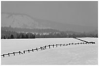 Wooden fence, snow-covered flat, hills in winter. Grand Teton National Park ( black and white)