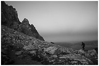 Mountaineer jumps on boulder at Lower Saddle,dusk. Grand Teton National Park ( black and white)
