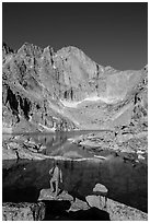 Hiker standing near Chasm Lake, looking at Longs peak. Rocky Mountain National Park, Colorado, USA. (black and white)