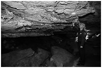 Ranger pointing at speleotherm in large cave room. Wind Cave National Park, South Dakota, USA. (black and white)
