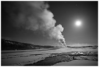 Old Faithful Geyser eruption and moon. Yellowstone National Park, Wyoming, USA. (black and white)