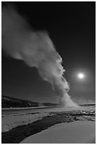 Night view of Old Faithful Geyser in winter with full moon. Yellowstone National Park, Wyoming, USA. (black and white)