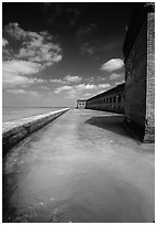 Fort Jefferson moat and massive brick wall on a sunny dayl. Dry Tortugas National Park ( black and white)