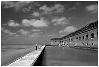 Tourists stroll on the seawall. Dry Tortugas National Park ( black and white)