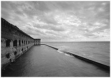 Fort Jefferson wall and moat with wave over seawall, cloudy weather. Dry Tortugas  National Park ( black and white)