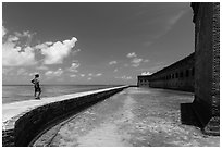 Park visitor looking, Fort Jefferson moat and seawall. Dry Tortugas National Park ( black and white)