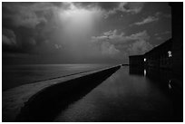 Fort Jefferson seawall at night with sky lit by thunderstorm. Dry Tortugas National Park ( black and white)