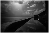 Fort Jefferson seawall at night with sky lit by tropical storm. Dry Tortugas National Park ( black and white)