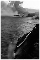 Bright molten lava flows into the Pacific Ocean, plume in background. Hawaii Volcanoes National Park ( black and white)