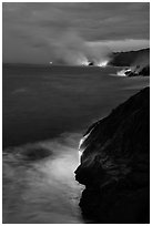 Molten lava pouring over sea cliffs at dawn. Hawaii Volcanoes National Park, Hawaii, USA. (black and white)
