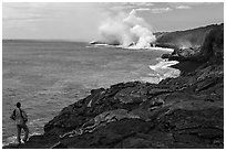 Park visitor looking, lava ocean entry plume. Hawaii Volcanoes National Park, Hawaii, USA. (black and white)
