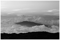 Puu Waawaa summit emerging from sea of clouds at sunset. Hawaii Volcanoes National Park, Hawaii, USA. (black and white)