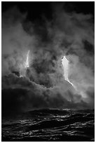 Lava cascading cliffs above ocean waves at night. Hawaii Volcanoes National Park ( black and white)