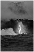 A single spigot of lava creates a large plume steam at sunrise upon reaching ocean. Hawaii Volcanoes National Park ( black and white)