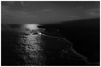 Aerial view of coastline with distant lava ocean entry and moonlight reflections at night. Hawaii Volcanoes National Park ( black and white)