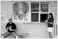 Shave ice store with man sitting eating and woman ordering, Waimanalo. Oahu island, Hawaii, USA (black and white)
