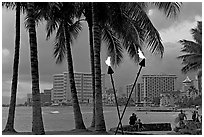 Waterfront at dusk with bare flame lamps. Waikiki, Honolulu, Oahu island, Hawaii, USA (black and white)