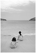 Two girls at the edge of water, Hanauma Bay. Oahu island, Hawaii, USA (black and white)