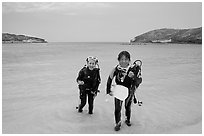 Scuba divers walking out of the water, Hanauma Bay. Oahu island, Hawaii, USA (black and white)