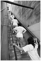 Women climbing a staircase on the Diamond Head summit trail. Oahu island, Hawaii, USA (black and white)