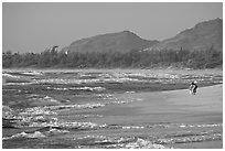 Woman with child on beach, Lydgate Park, early morning. Kauai island, Hawaii, USA (black and white)