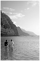 Couple looking at the Na Pali Coast, Kee Beach, late afternoon. Kauai island, Hawaii, USA (black and white)