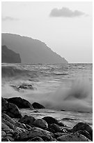 Boulders, waves, and Na Pali cliffs, sunset. Kauai island, Hawaii, USA (black and white)