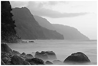Boulders, surf, and Na Pali cliffs, sunset. Kauai island, Hawaii, USA (black and white)