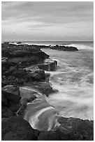 Surf and volcanic shore at sunset, South Point. Big Island, Hawaii, USA ( black and white)