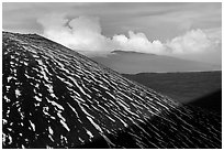 Cinder cone with snow stripes, distant clouds. Mauna Kea, Big Island, Hawaii, USA ( black and white)