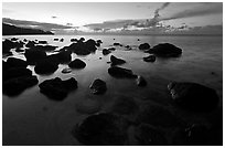 Boulders in water near Kalihika Park, sunset. Kauai island, Hawaii, USA ( black and white)