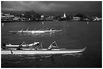 Outrigger canoes and town under storm sky, Kailua-Kona. Hawaii, USA ( black and white)